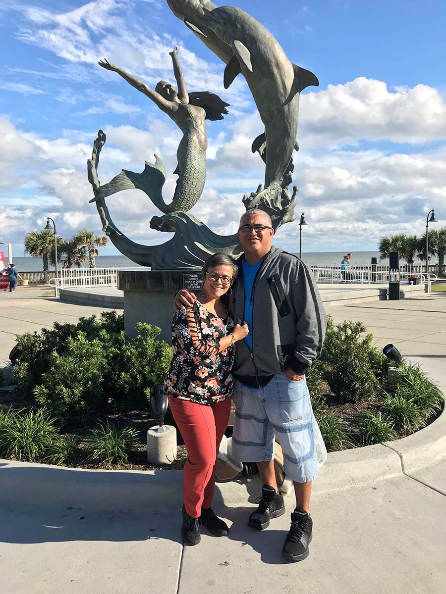 older couple posing together in front of mermaid statue