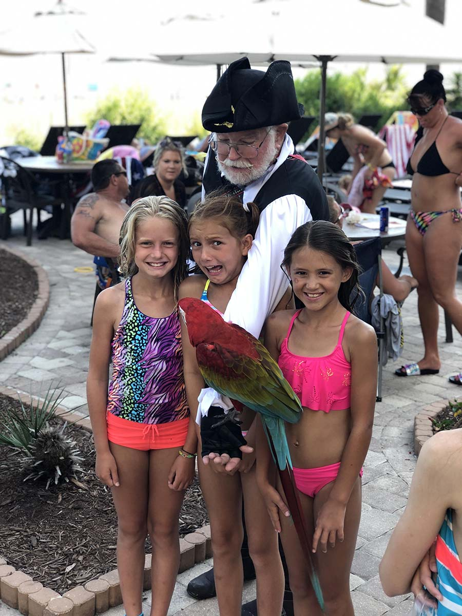 three girls posing with the parrot guy at pool deck