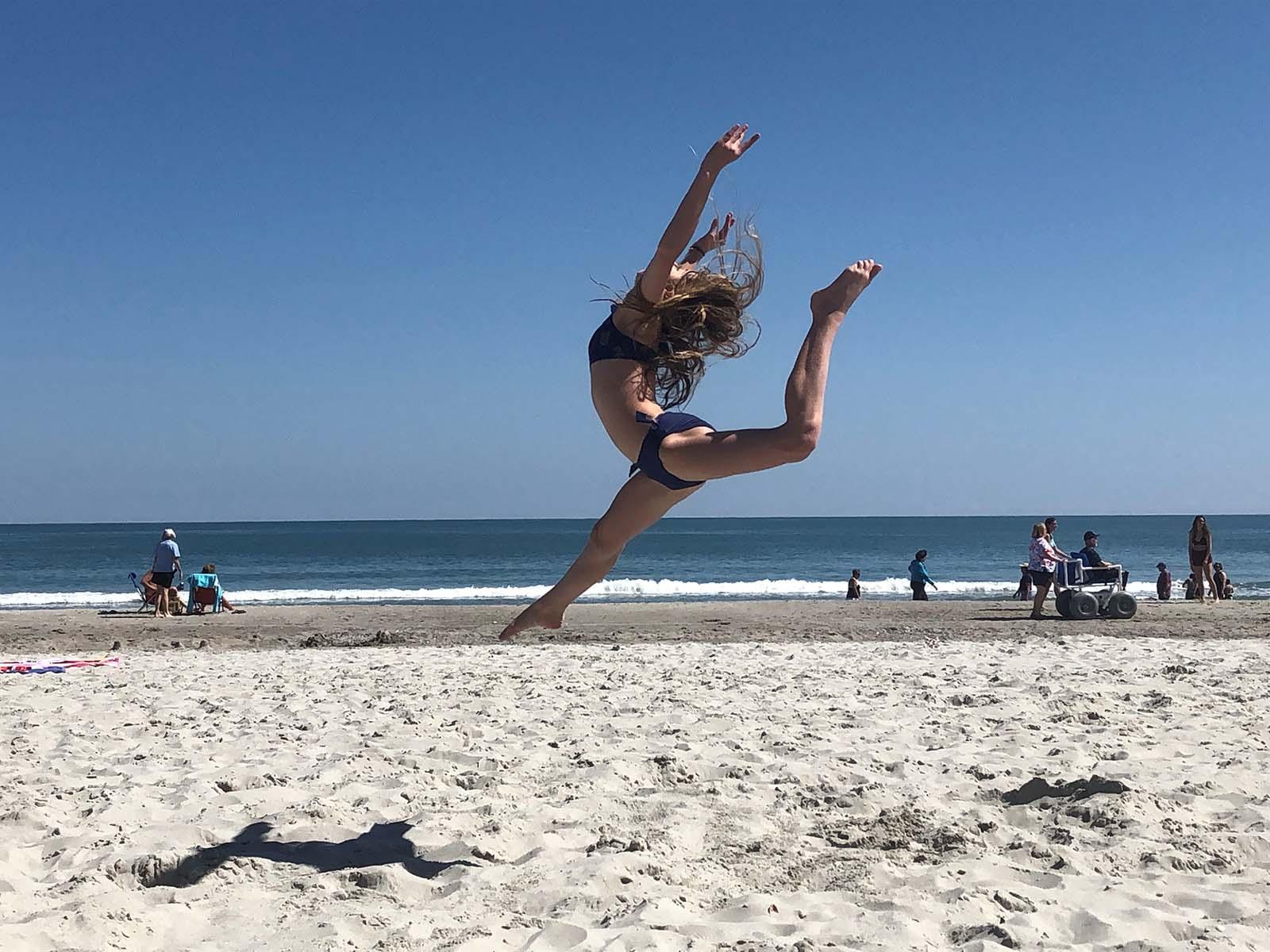 girl doing gymnastics on beach