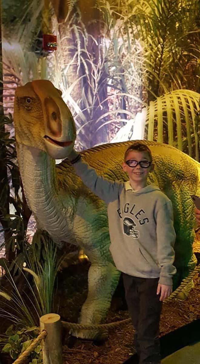 Little boy standing next to the dinosaur