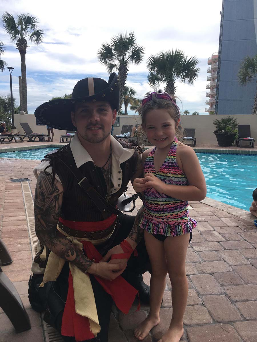 Little girl on pool deck taking a picture with pirate