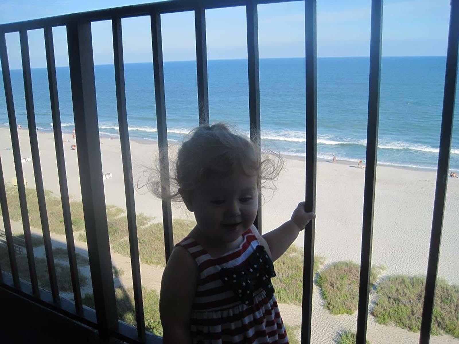 baby girl holding onto balcony