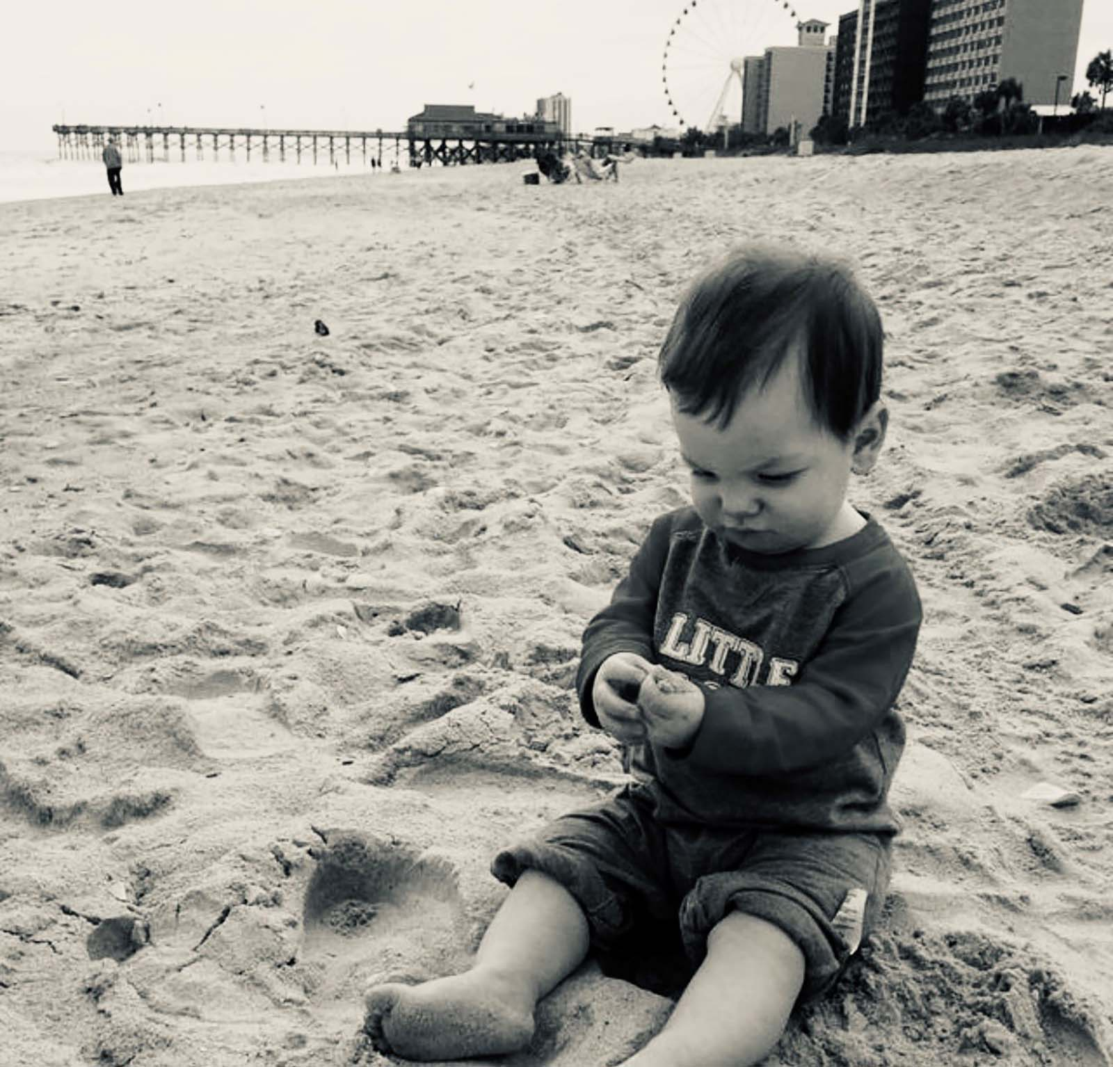 little boy sitting playing with sand
