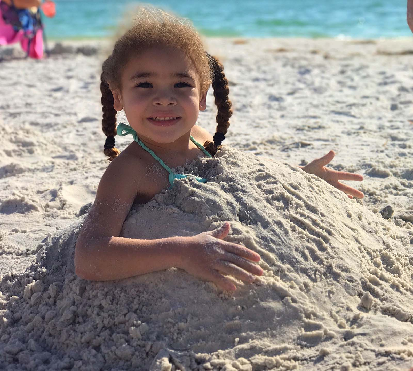 little girl sitting buried underneath the sand