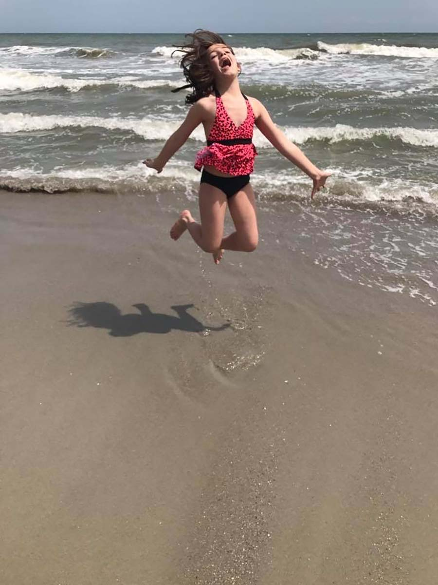 young girl jumping in the air in the ocean