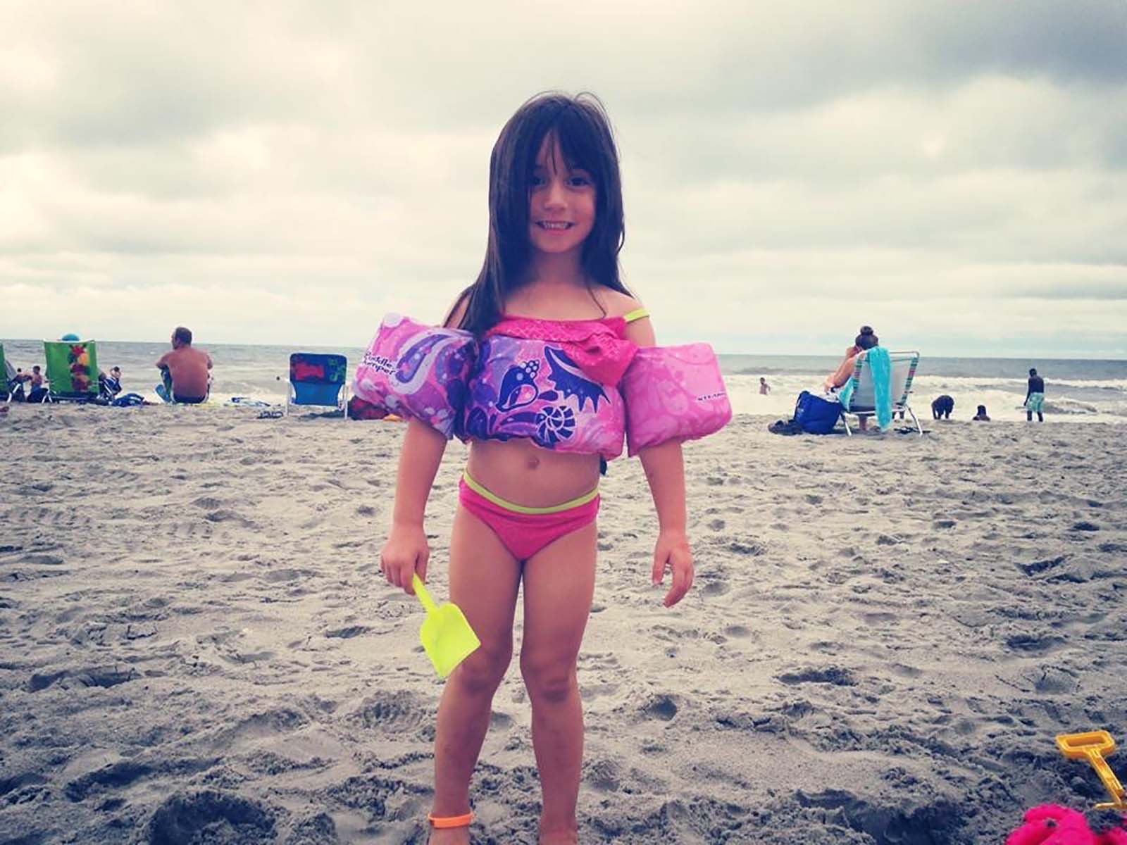 little girl holding shovel with swimmies on the beach