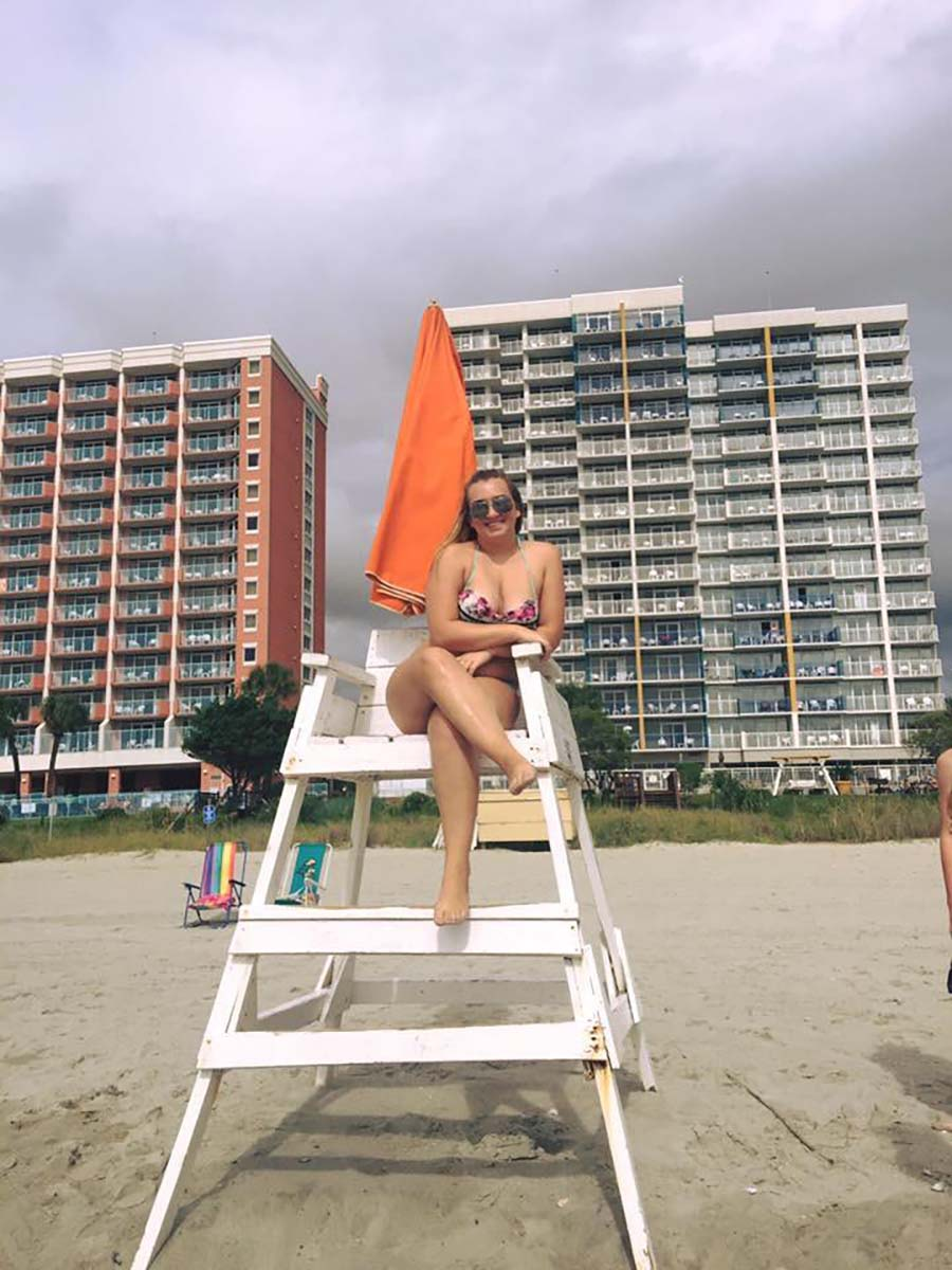 teenage girl sitting on lifeguard stand in front of resort