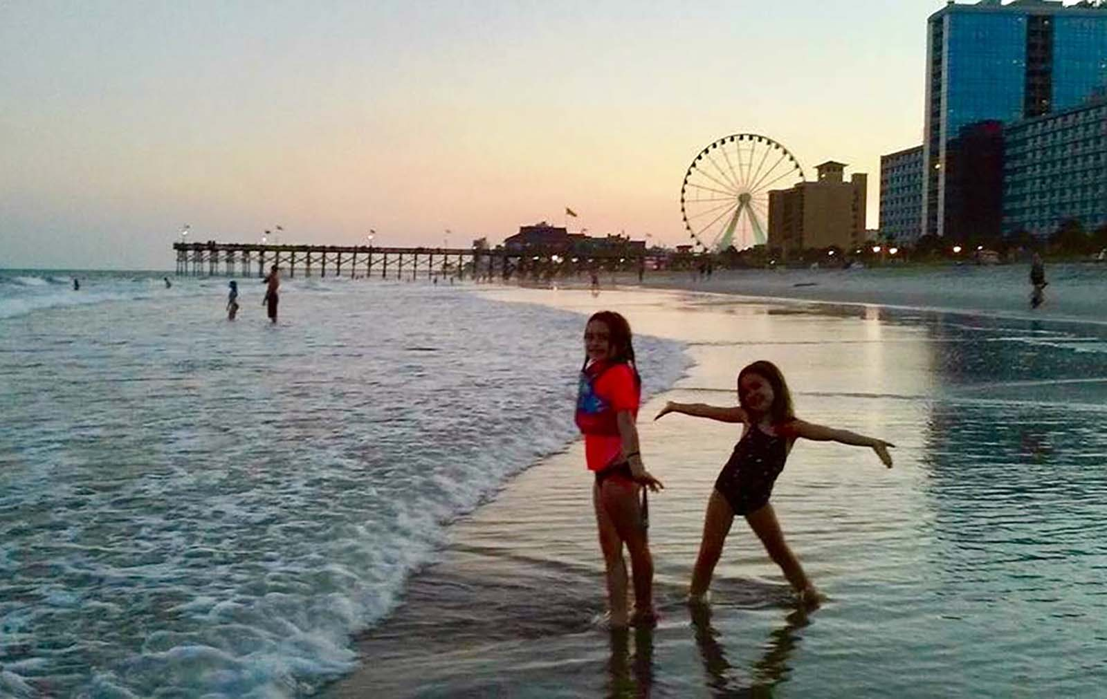 Two girls posing in the ocean with skywheel in the back