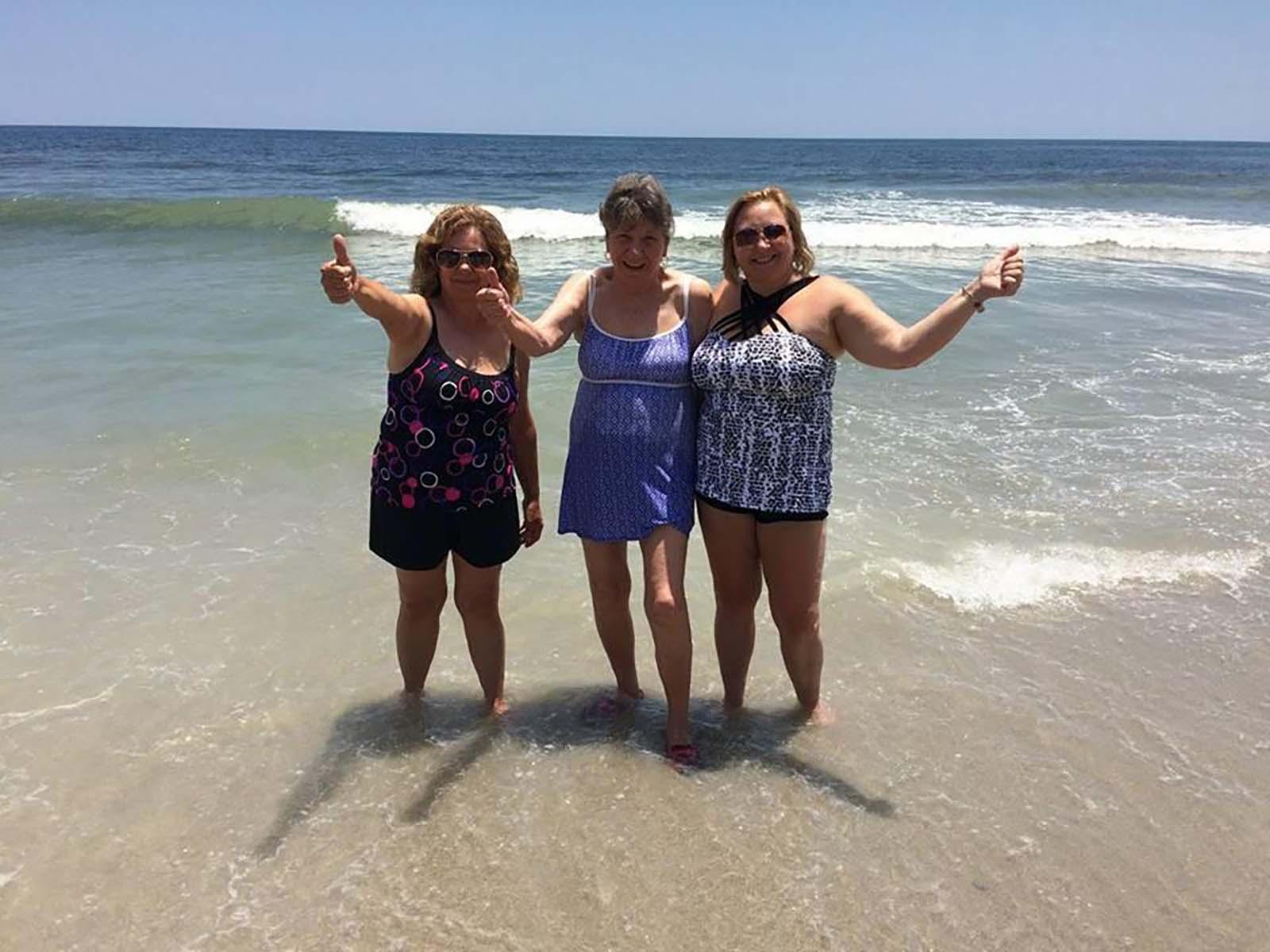 Three older women smiling in ocean