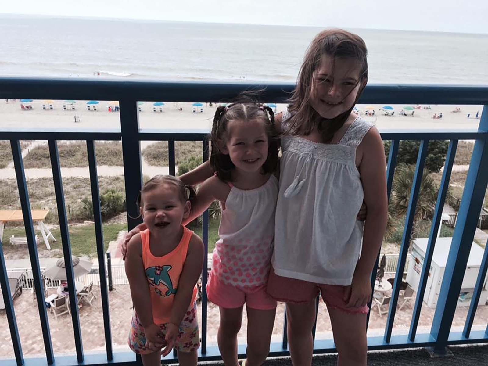 three little girls smiling on balcony