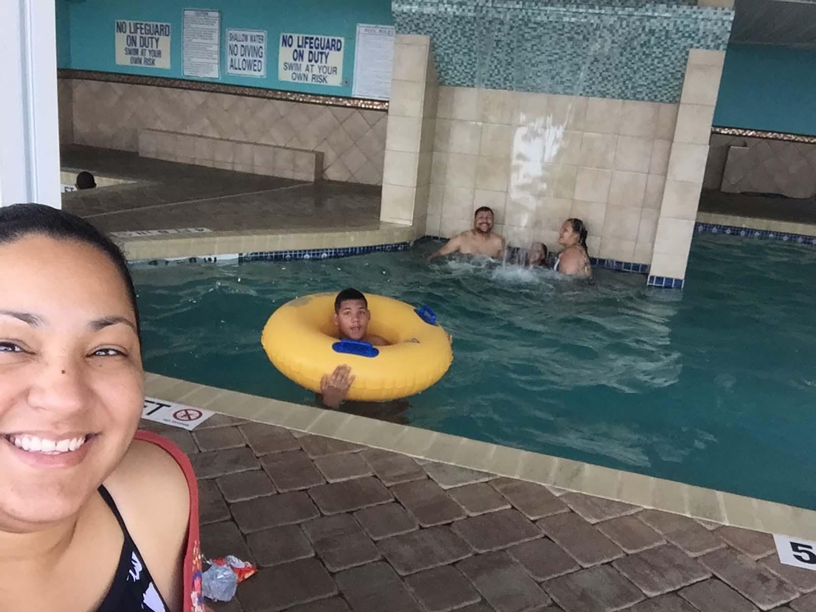 Mom taking selfie with kids in indoor pool behind