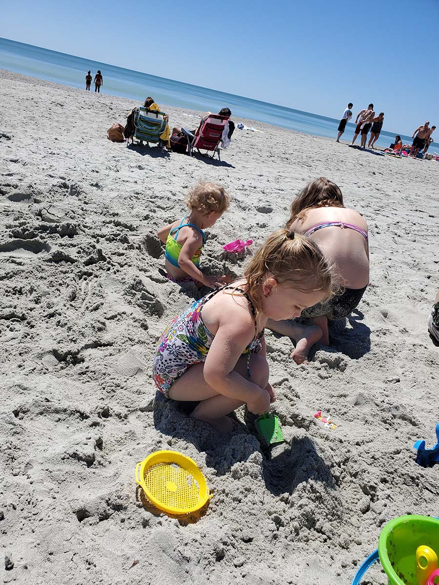 three girls digging around in the sand on the beach