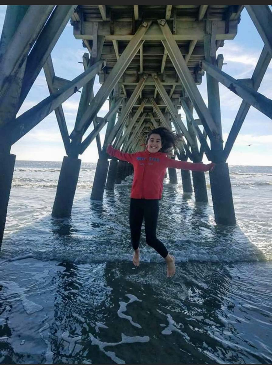 girl jumping in air underneath the pier