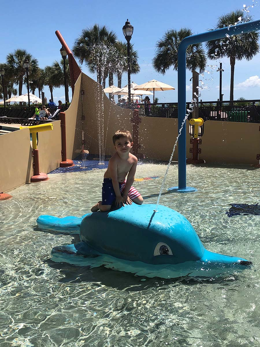 little boy cutely sittin on dolphin in kiddie pool