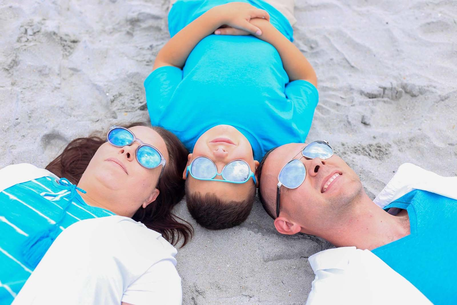 mom, dad, and son laying with heads together on beach