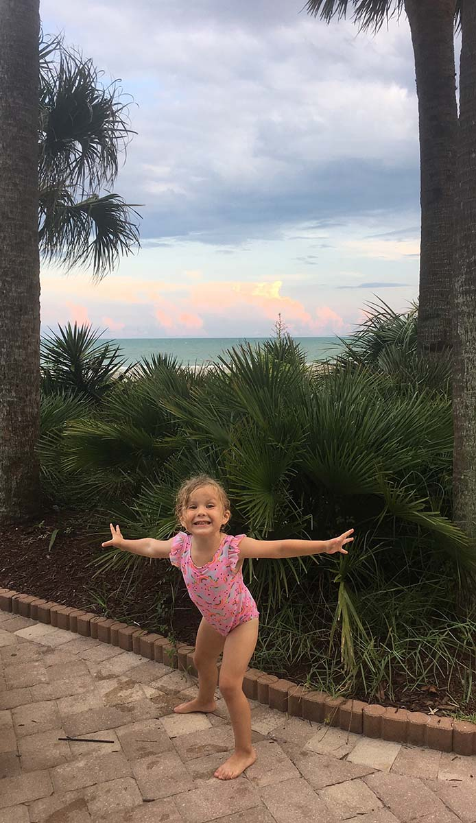 little girl excited to be at the beach in front of palm tree