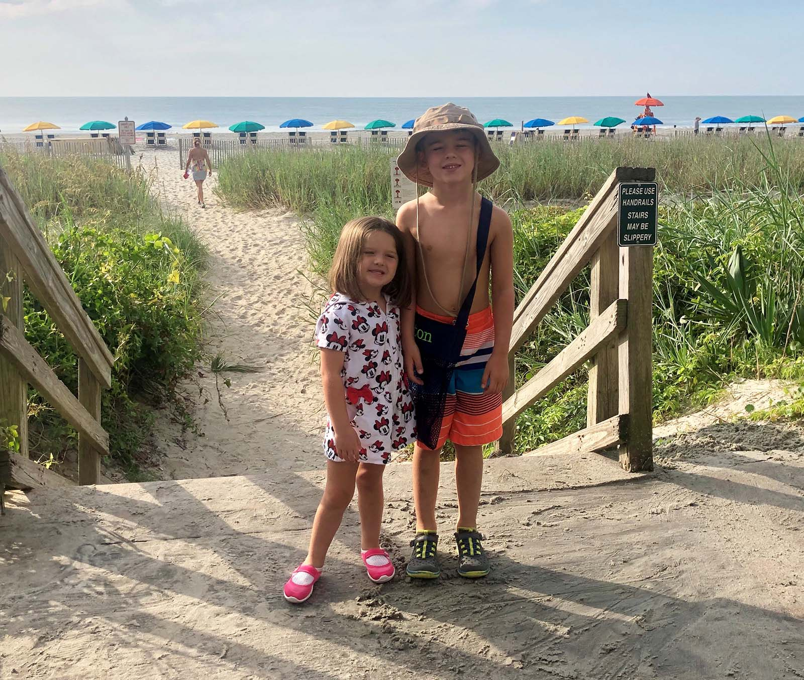 little boy and girl standing next to each other on the beach