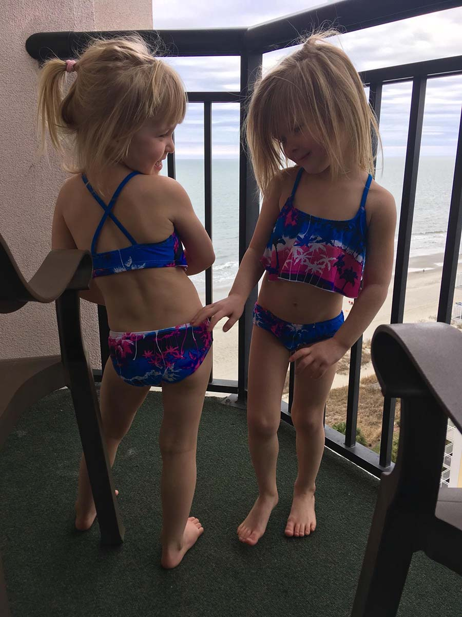 two little blonde twin girls posing on balcony of resort