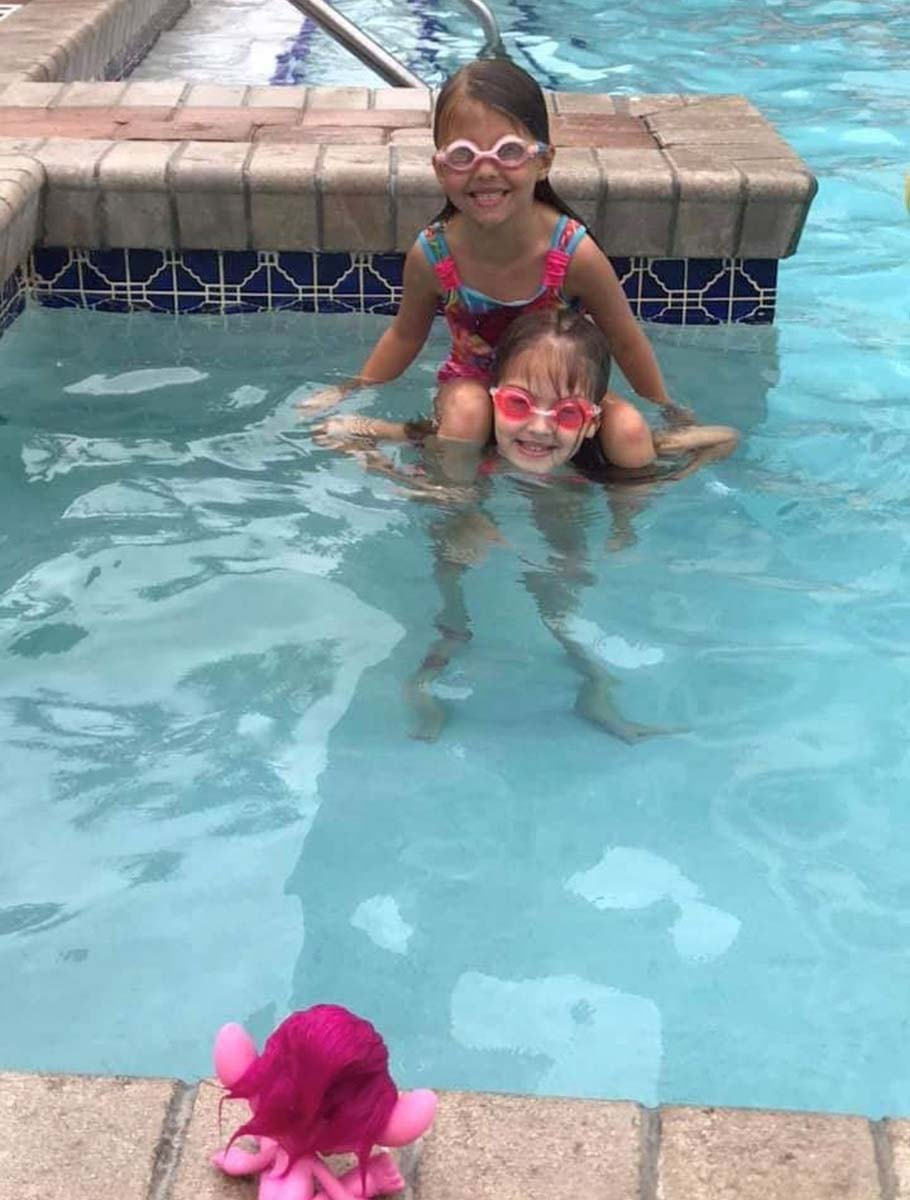 sisters swimming together in pool