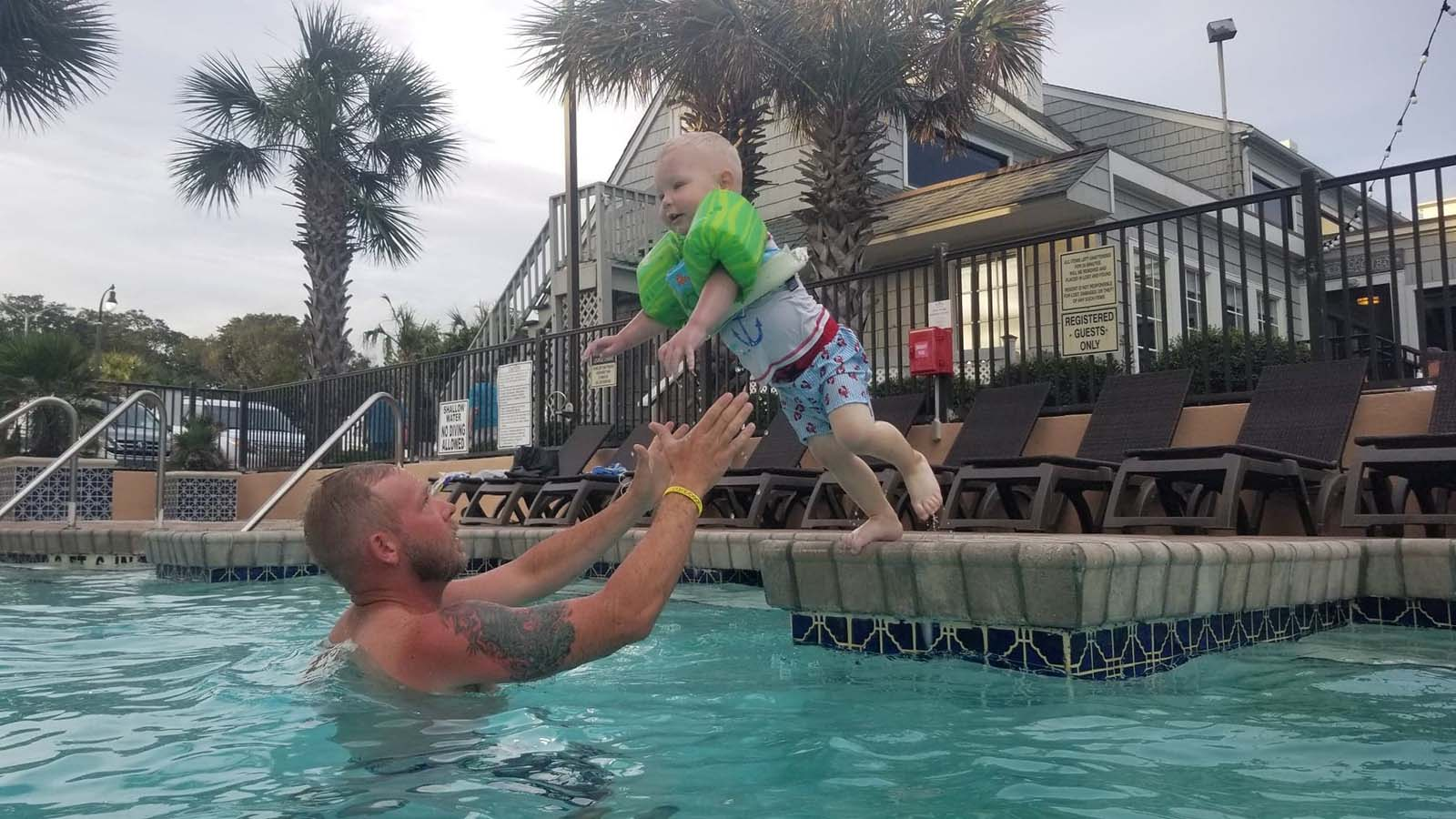 little boy jumping into fathers arms in the pool
