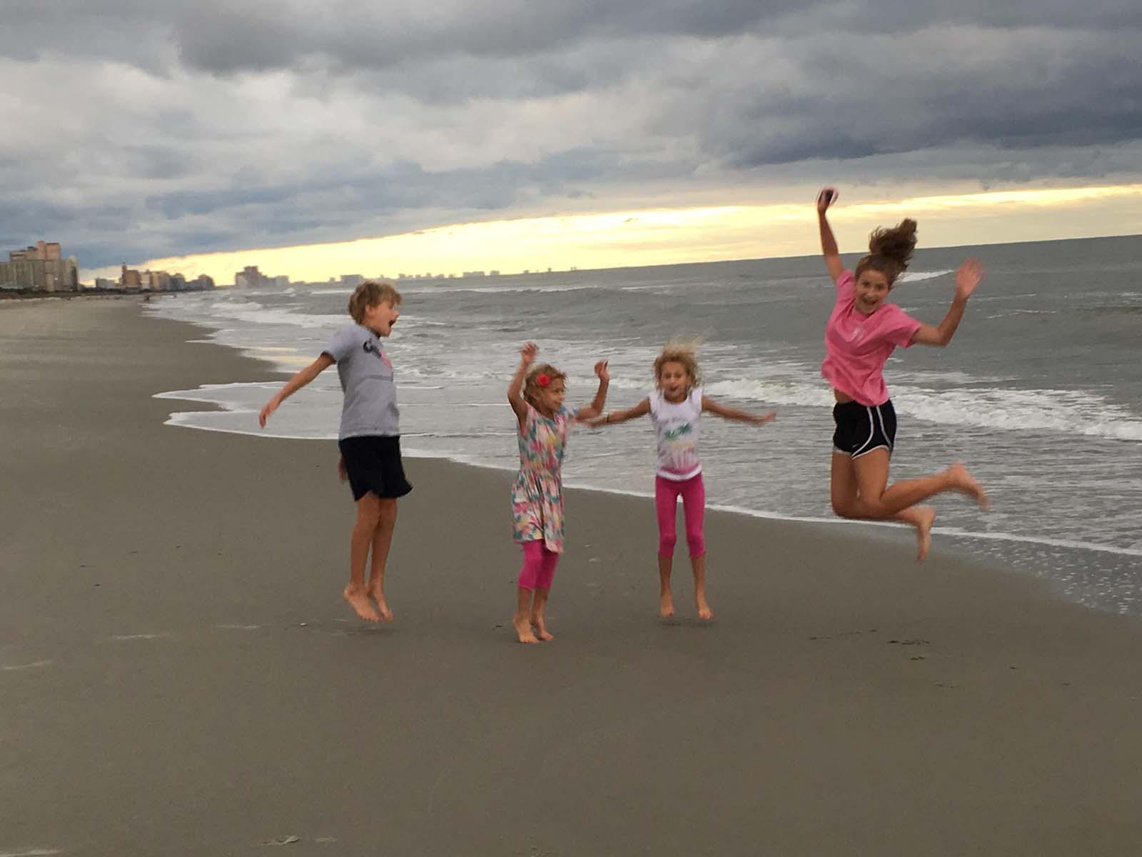 siblings jumping on beach at sunrise
