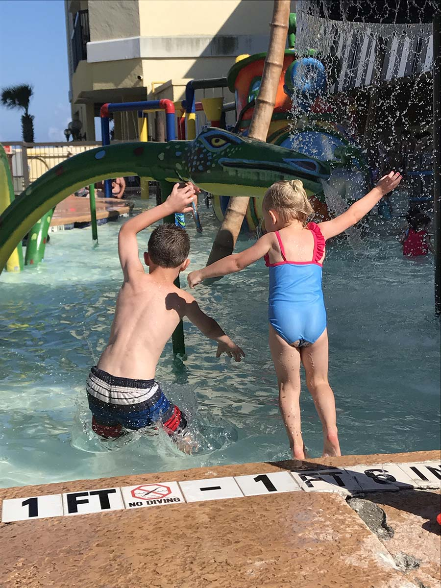 Two kids jumping into the pool