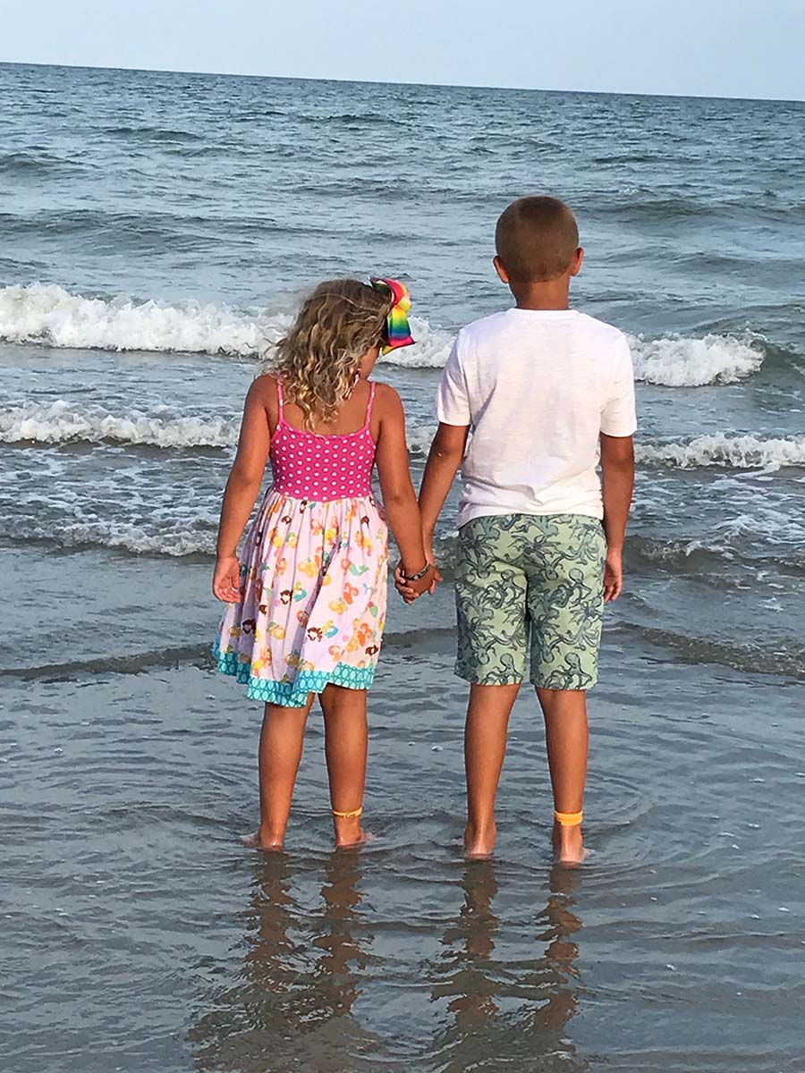Little boy and girl holding hands in the ocean