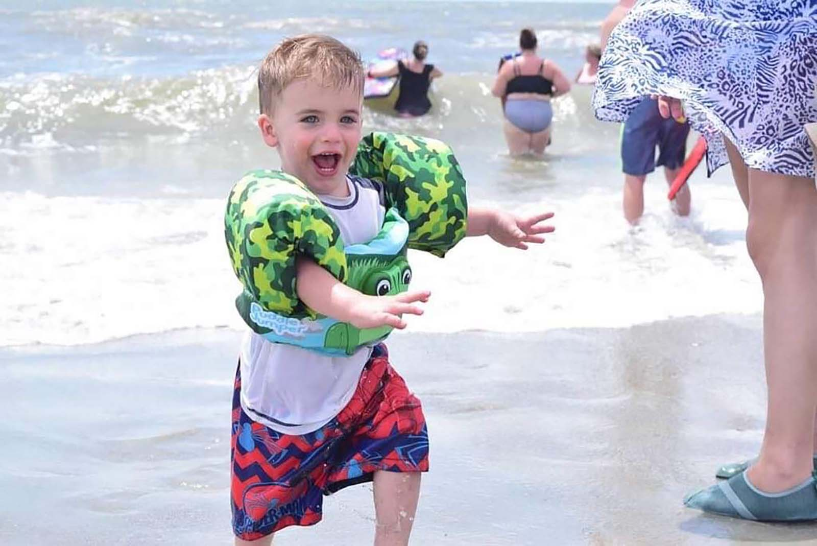 Little boy with green swimmies running in ocean