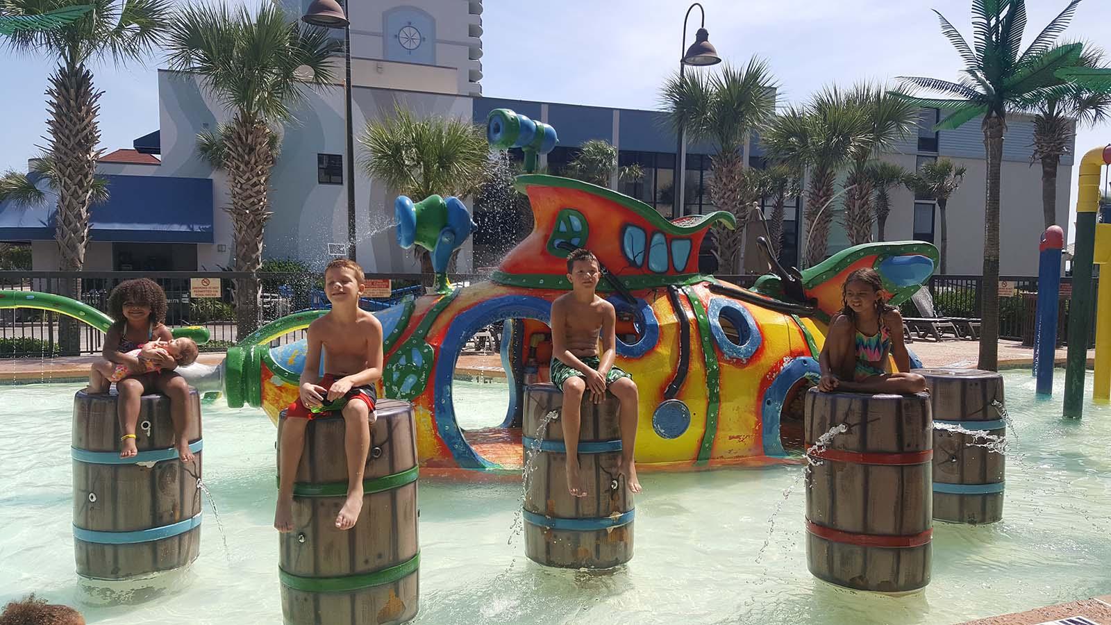 Multiple kids sitting on barrels in waterpark