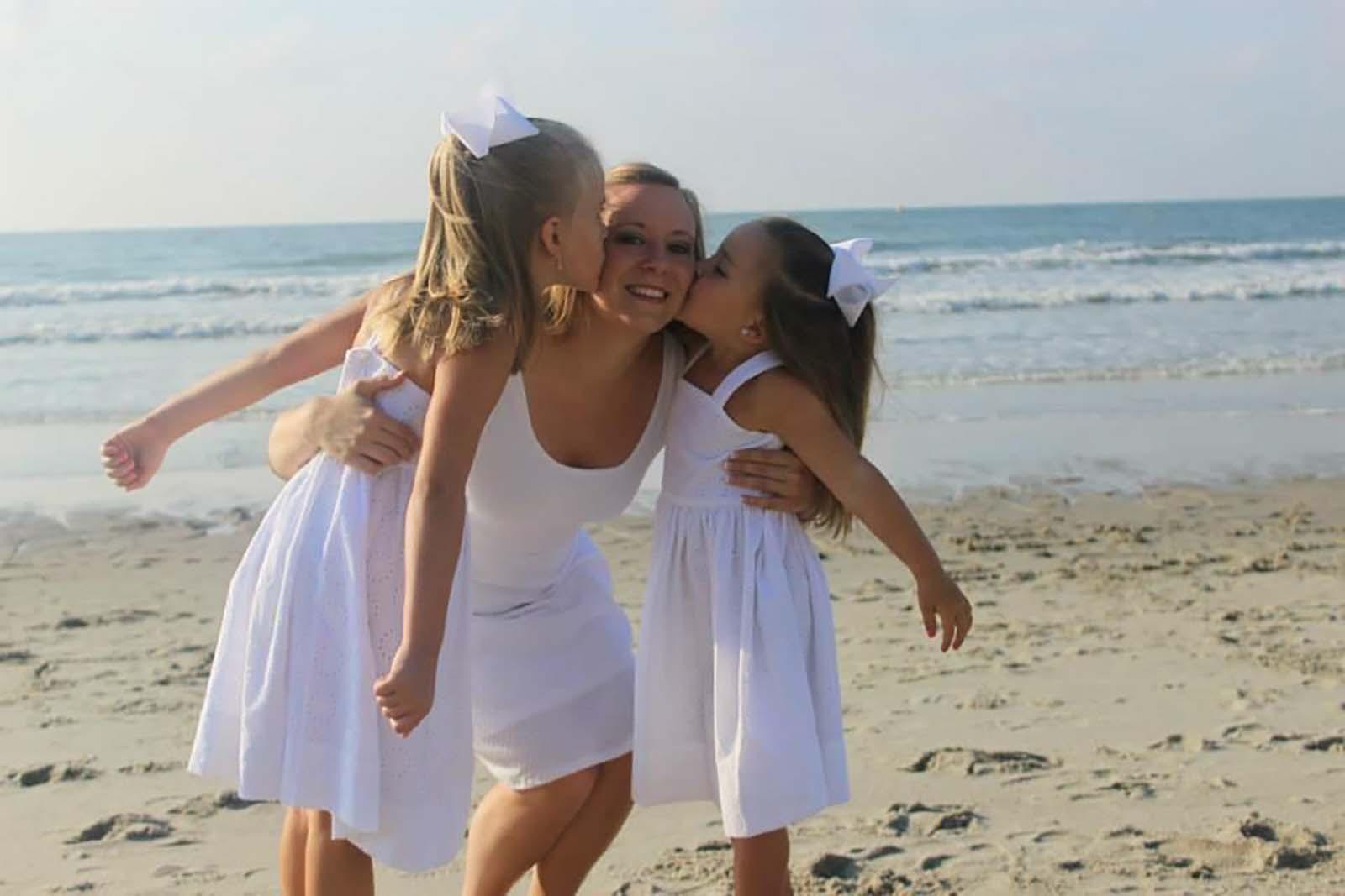 Two girls kissing mom on beach