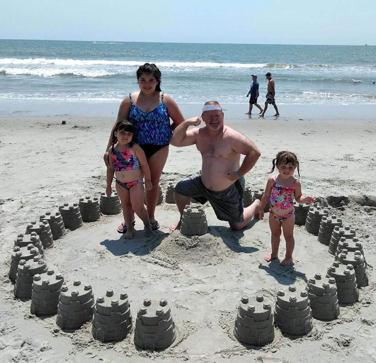 Family surrounded by sand castle ring