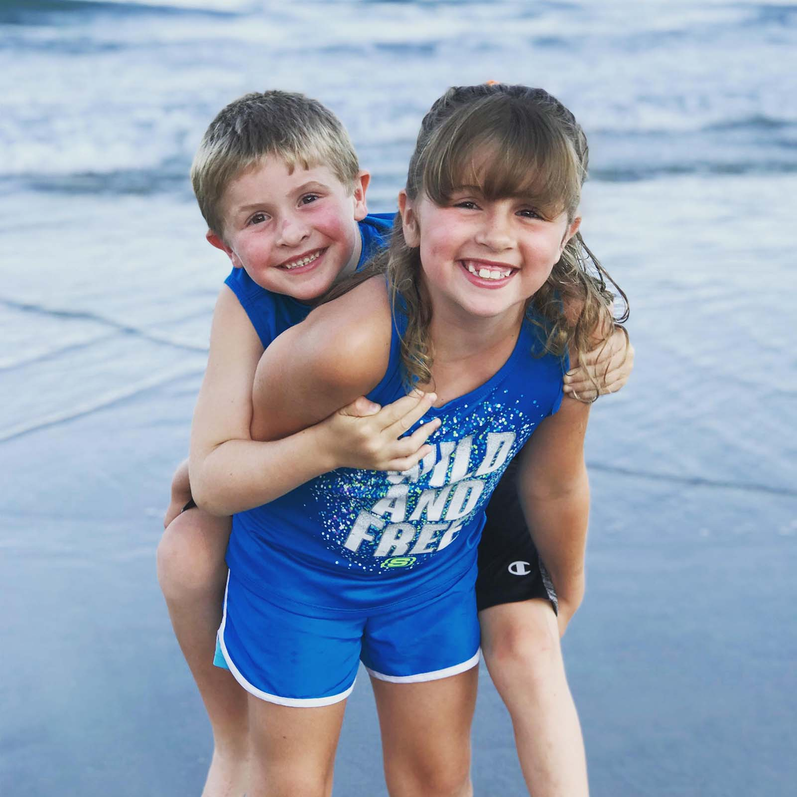 Girl with little brother on back in ocean