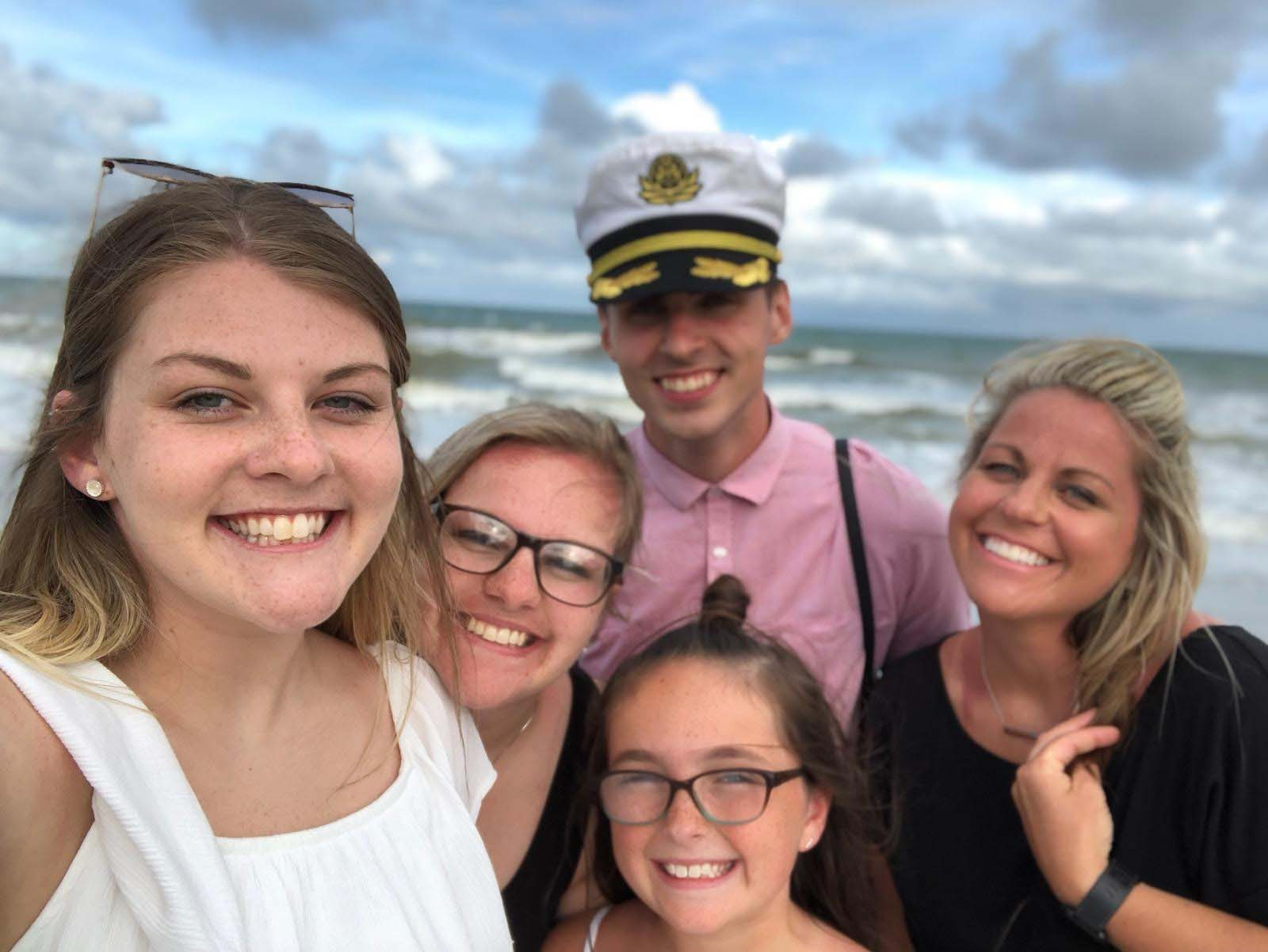 Family selfie on beach with boy in sailors hat