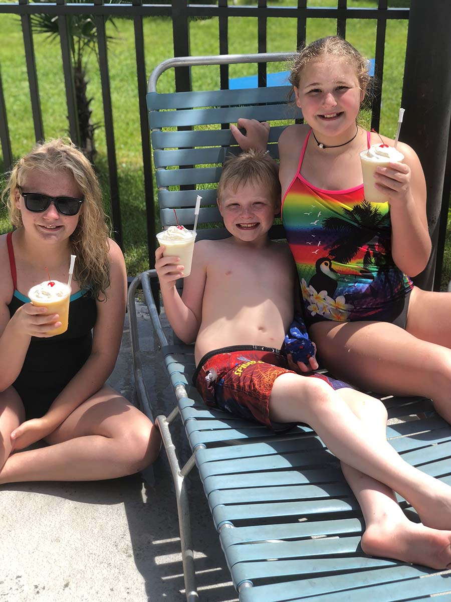 Three kids sitting and eating water ice by pool