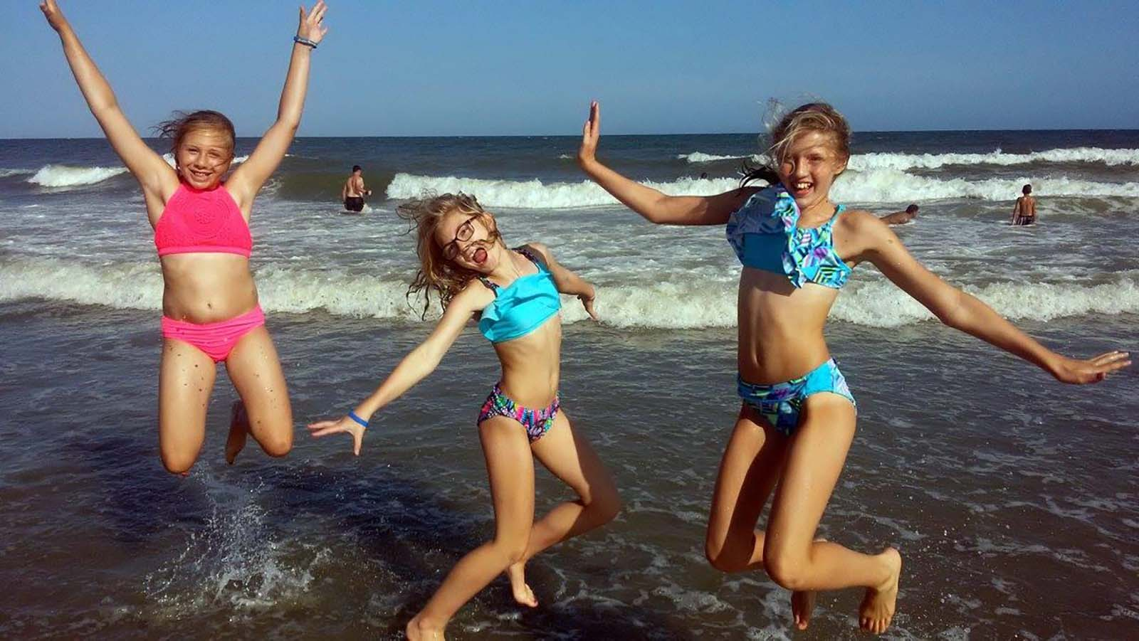 The girls jumping in the air in ocean