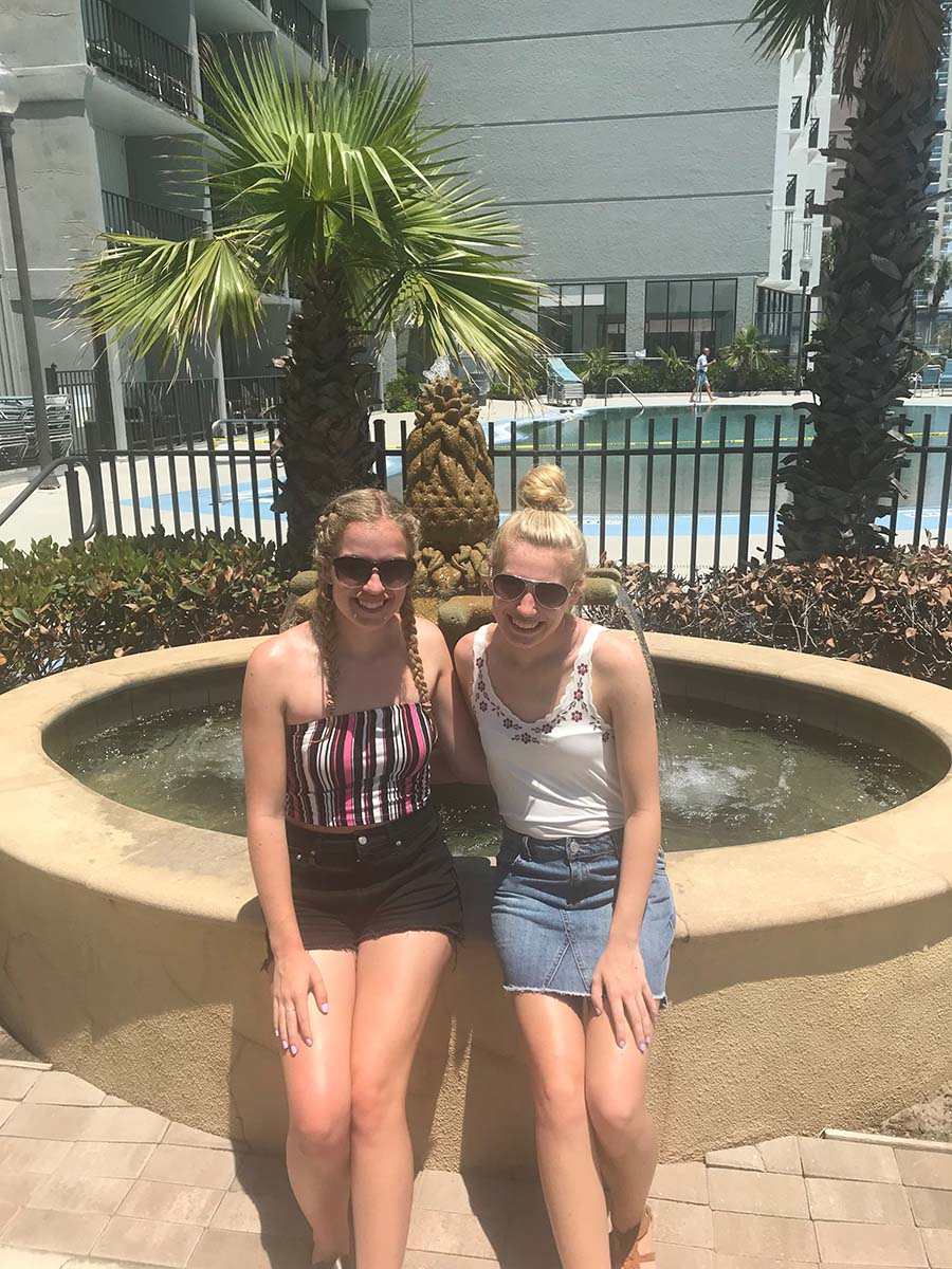Two sisters sitting on fountain together