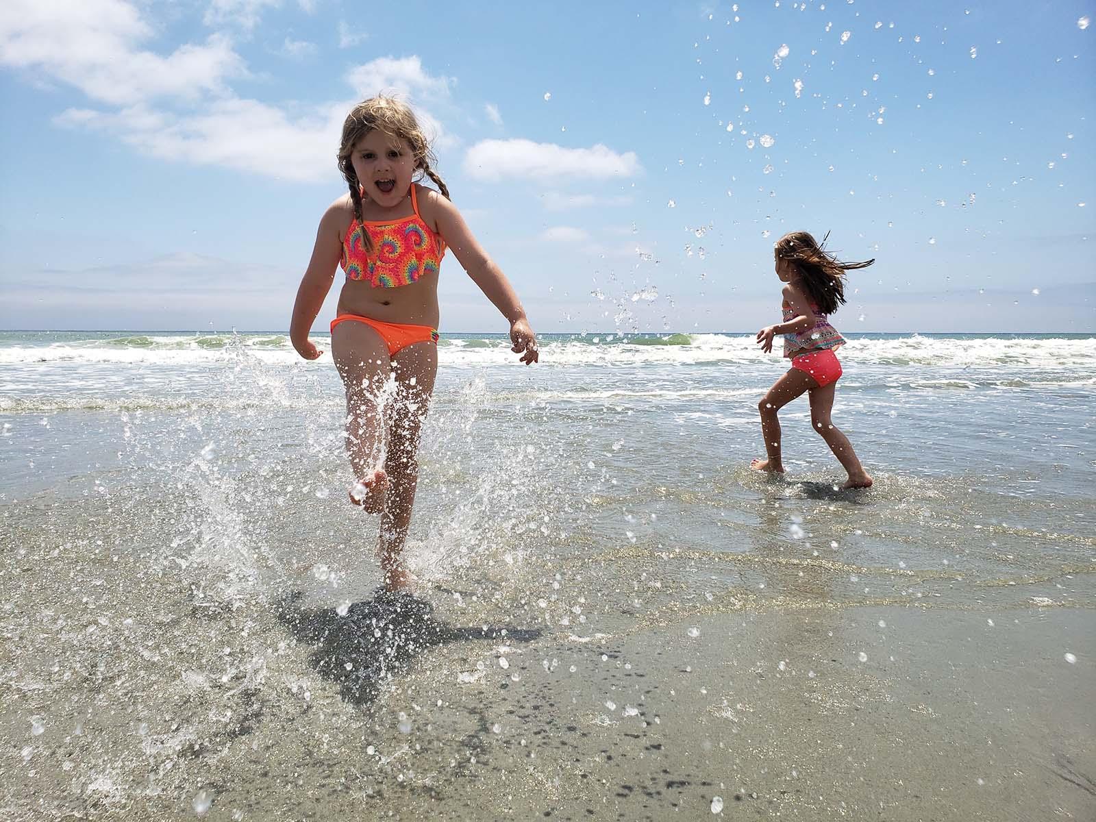 Two girls splashin around in the ocean