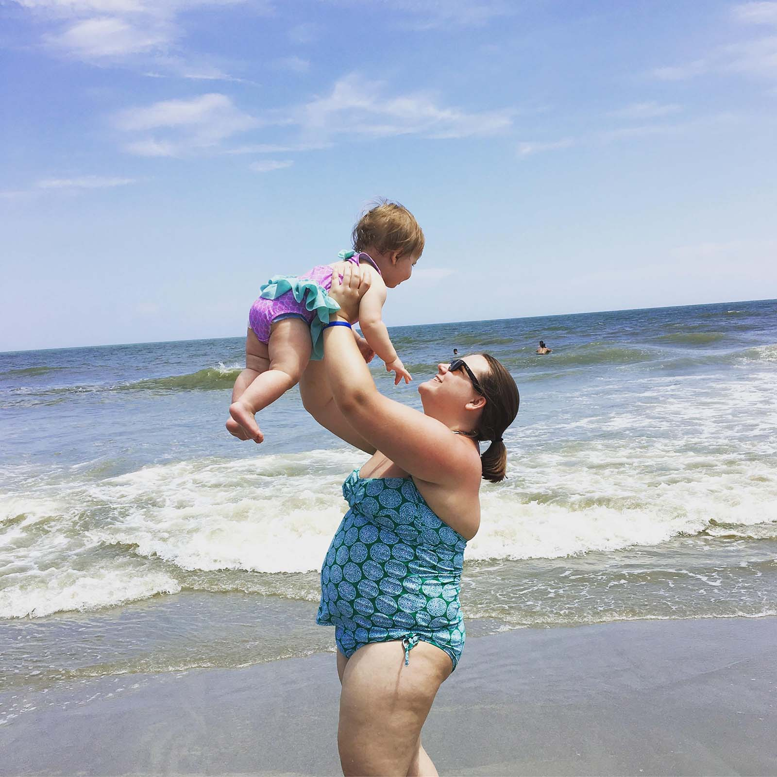 Mom holding up baby girl in air on the beach