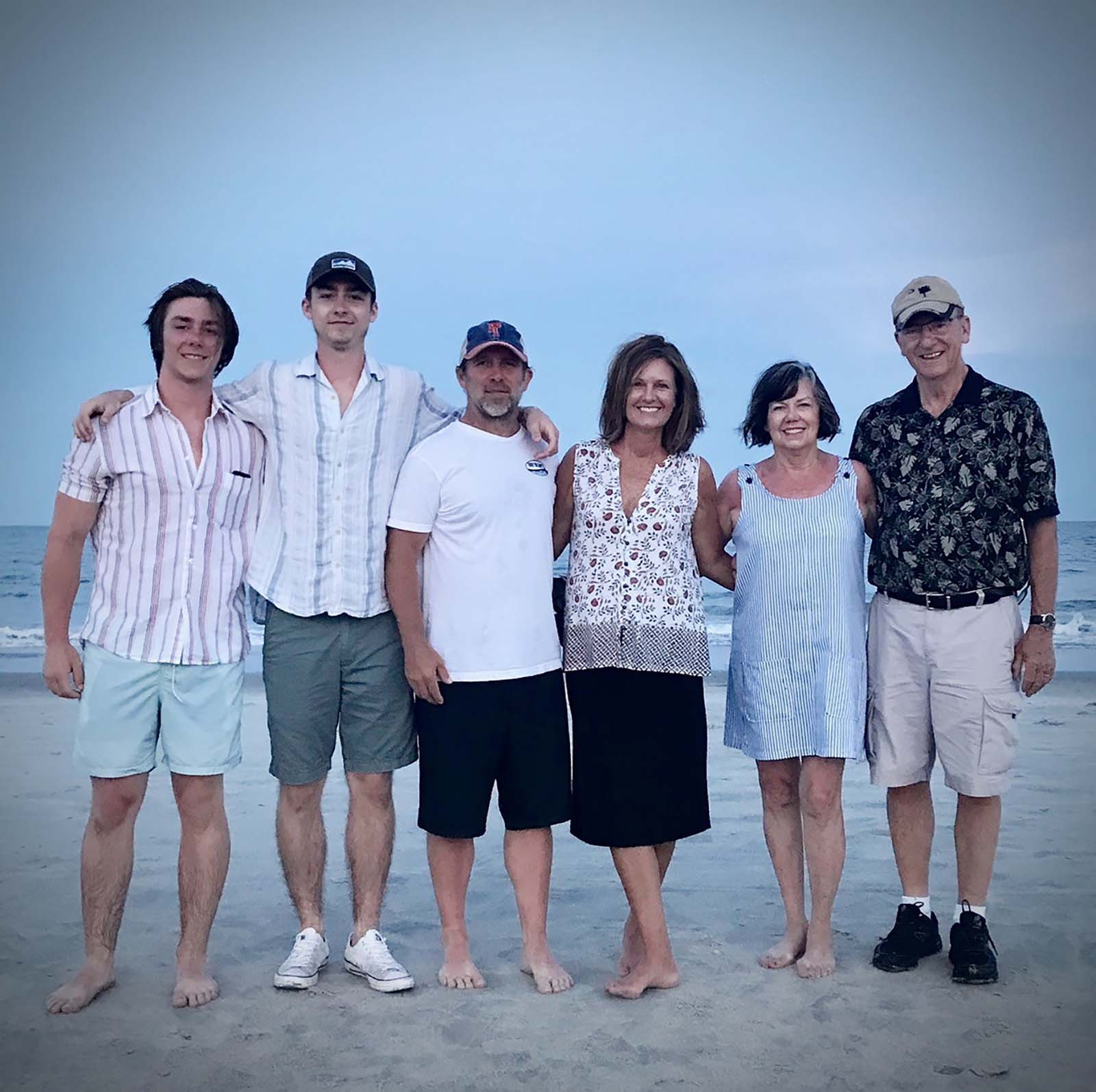 Family on the beach together wearing light clothing