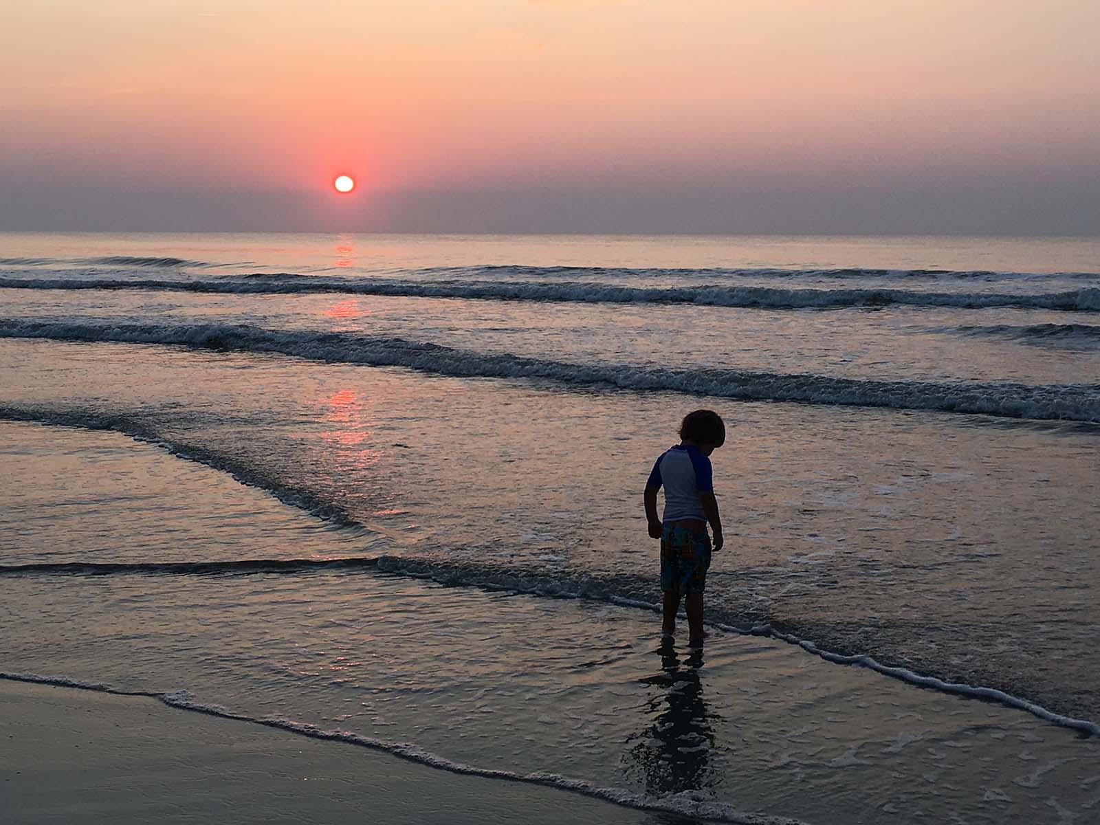Little boy on the beach at sunrise