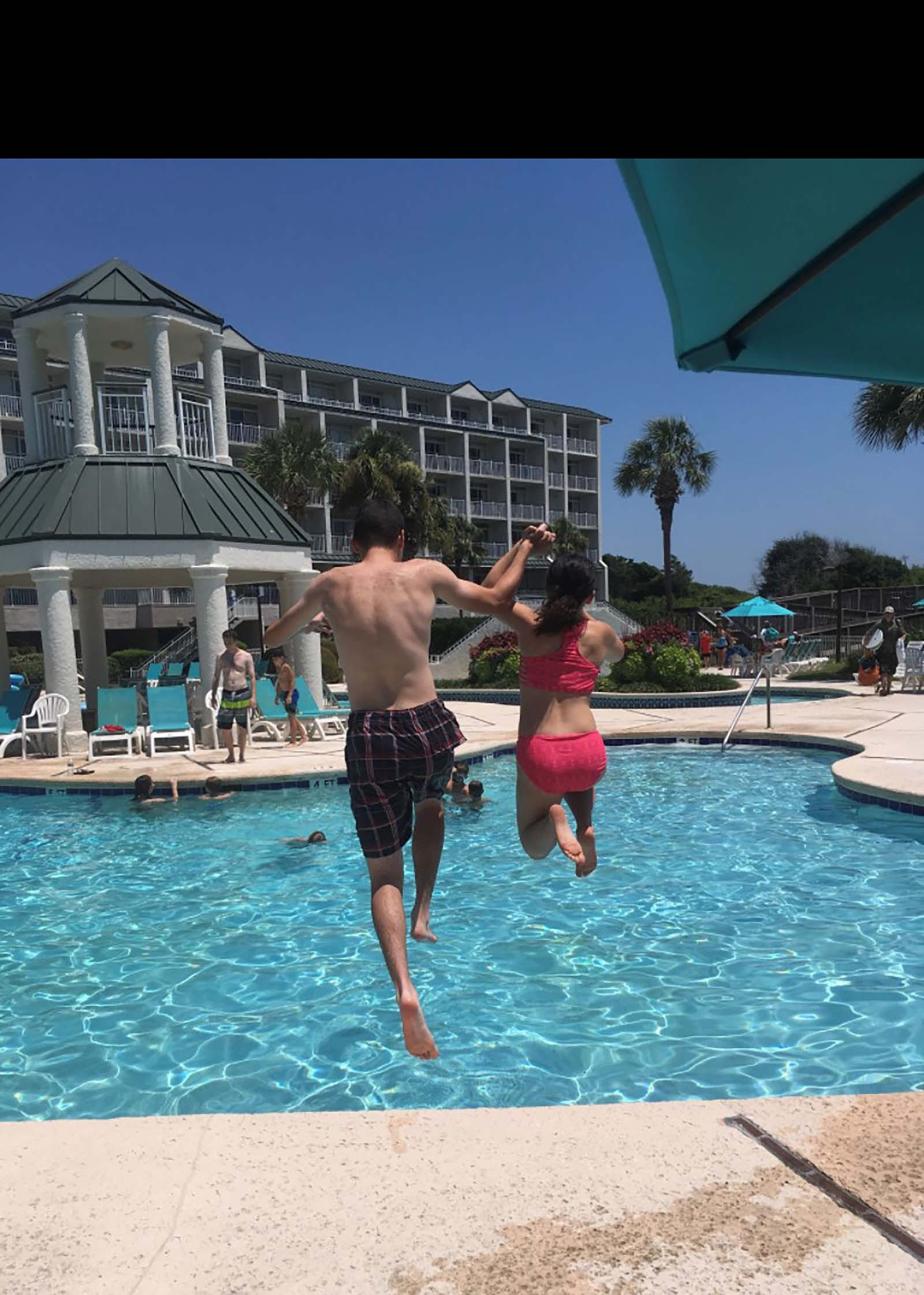 Siblings jumping into pool together