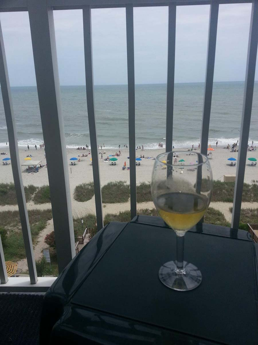 Glass of wine sitting on a table on the balcony