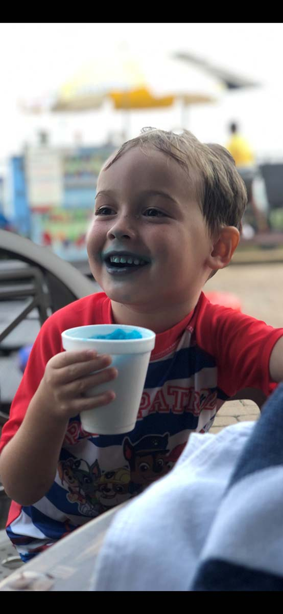 Boy laughing with snow cone on his face and hands