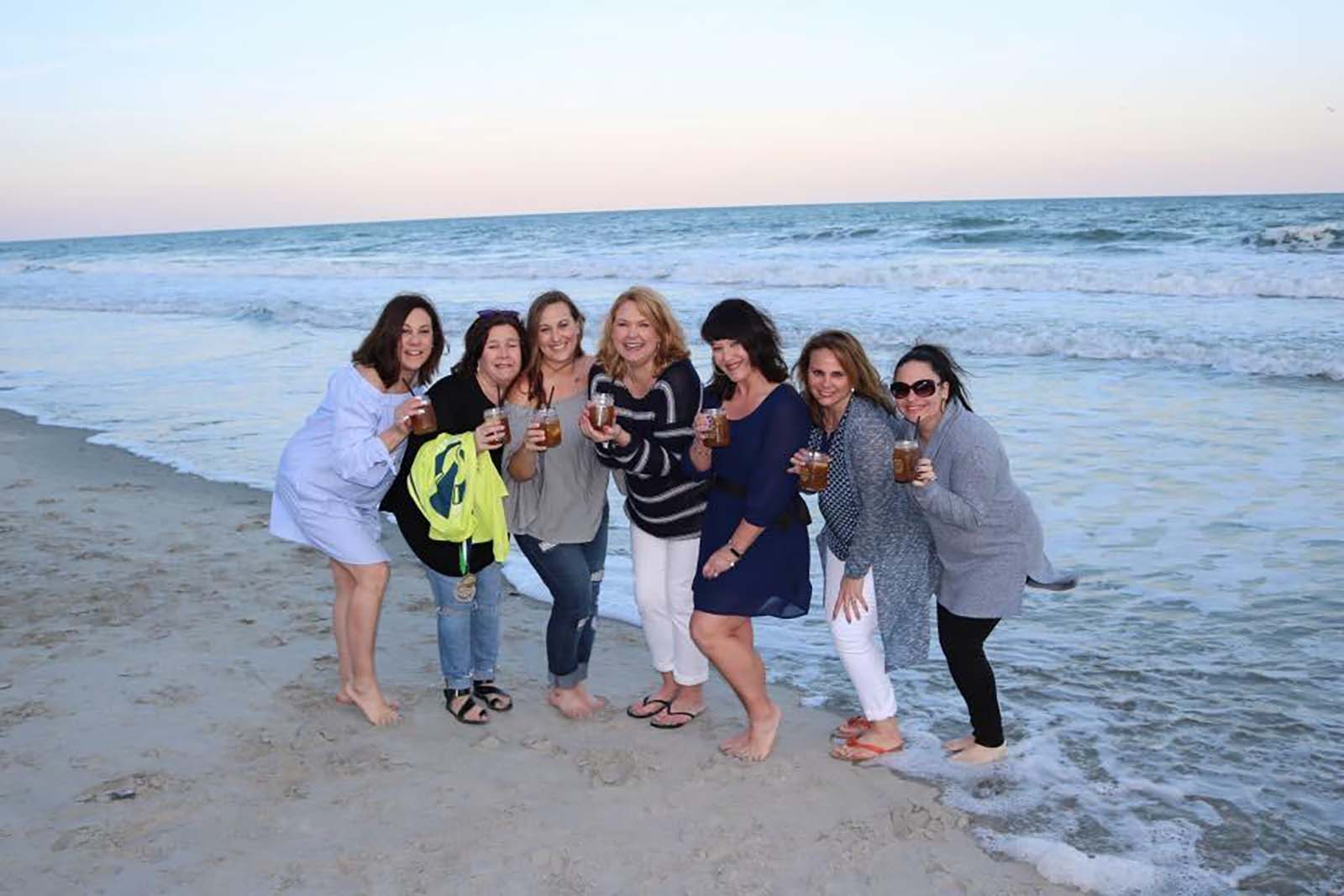 Group of girls in ocean with drinks