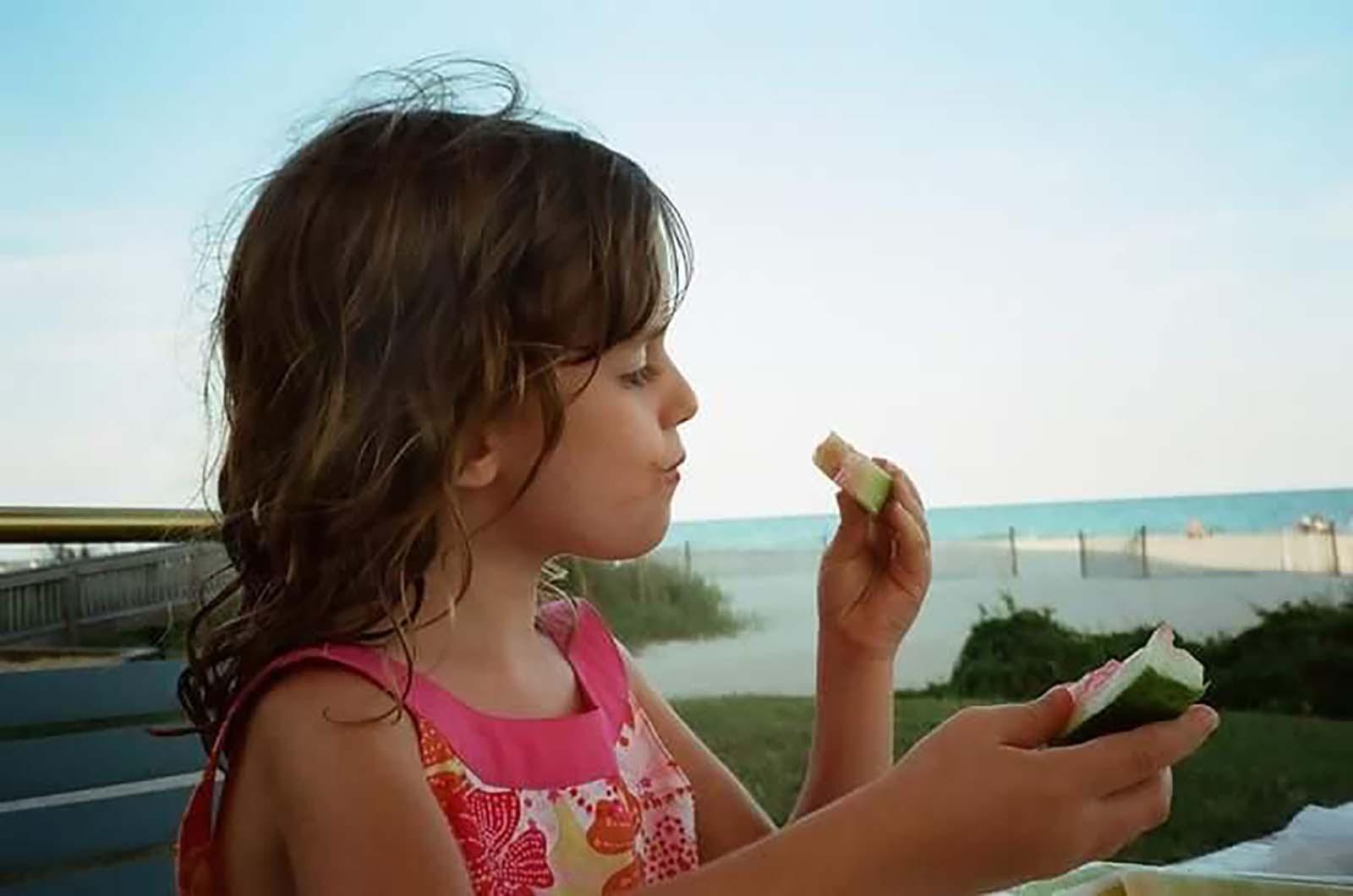 Little girl eating watermelon by beach