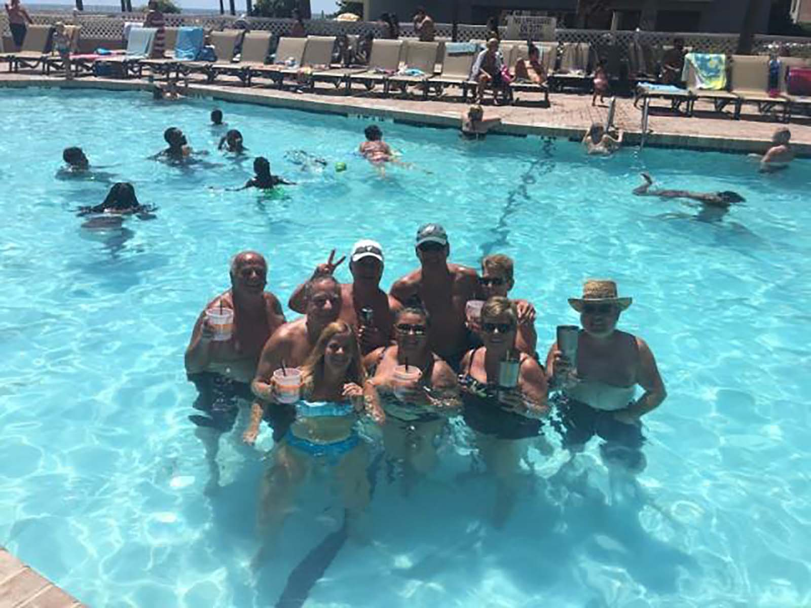 Group of adults with drinks in pool