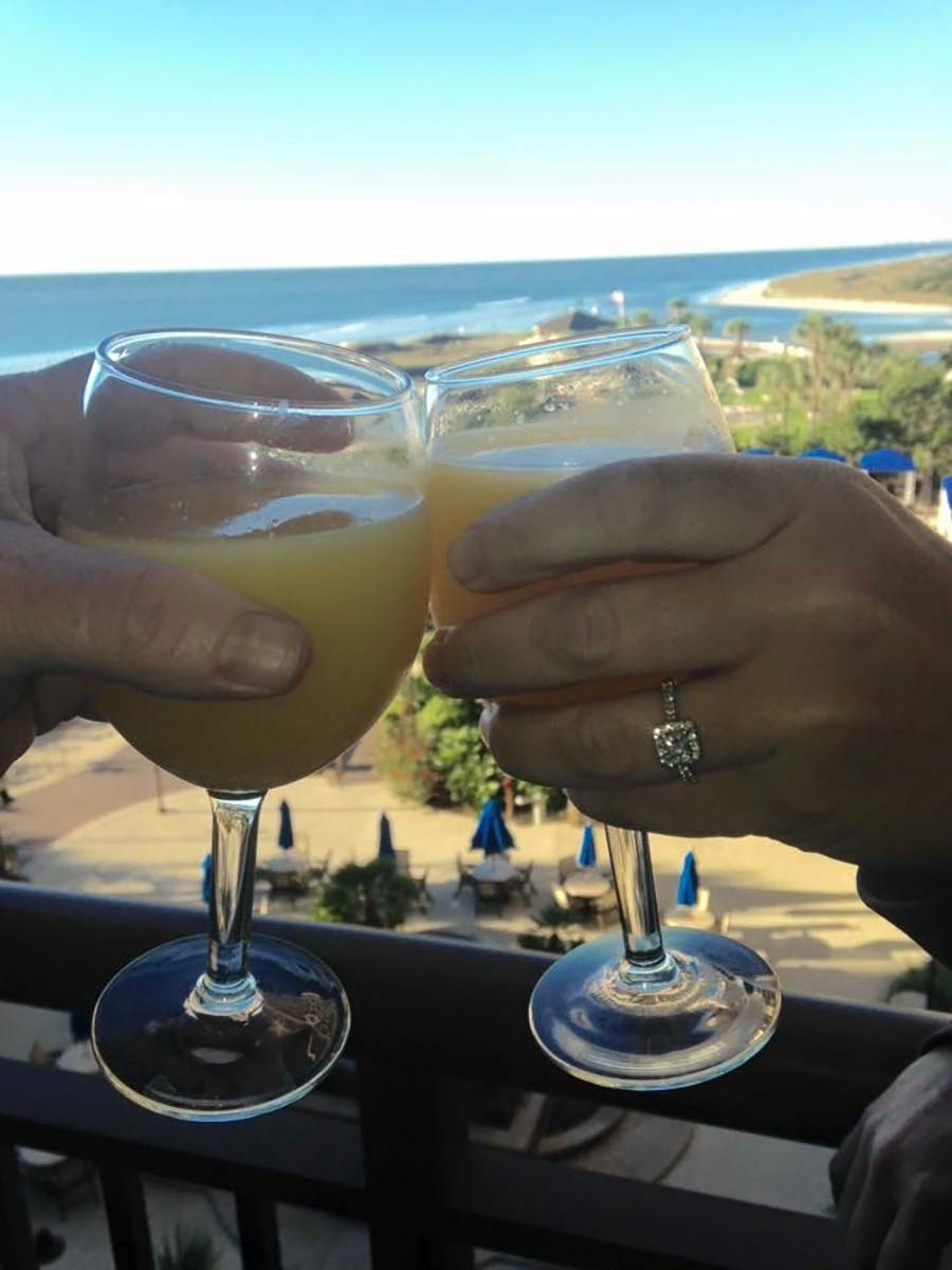 Clinking mimosas on balcony