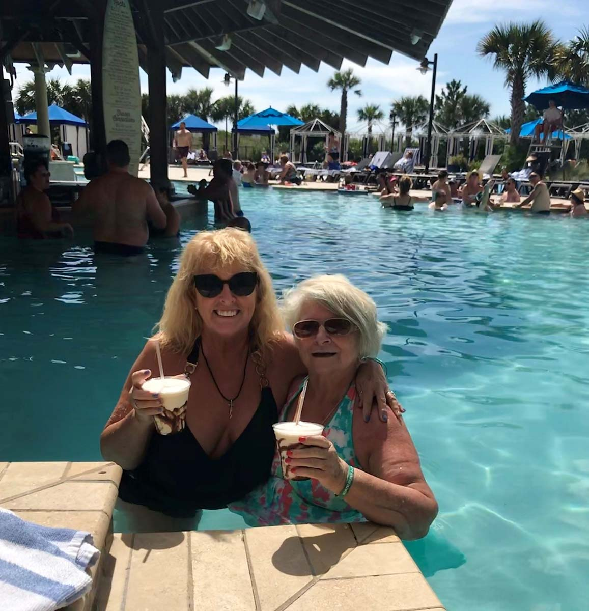 Two older ladies in pool with cocktails