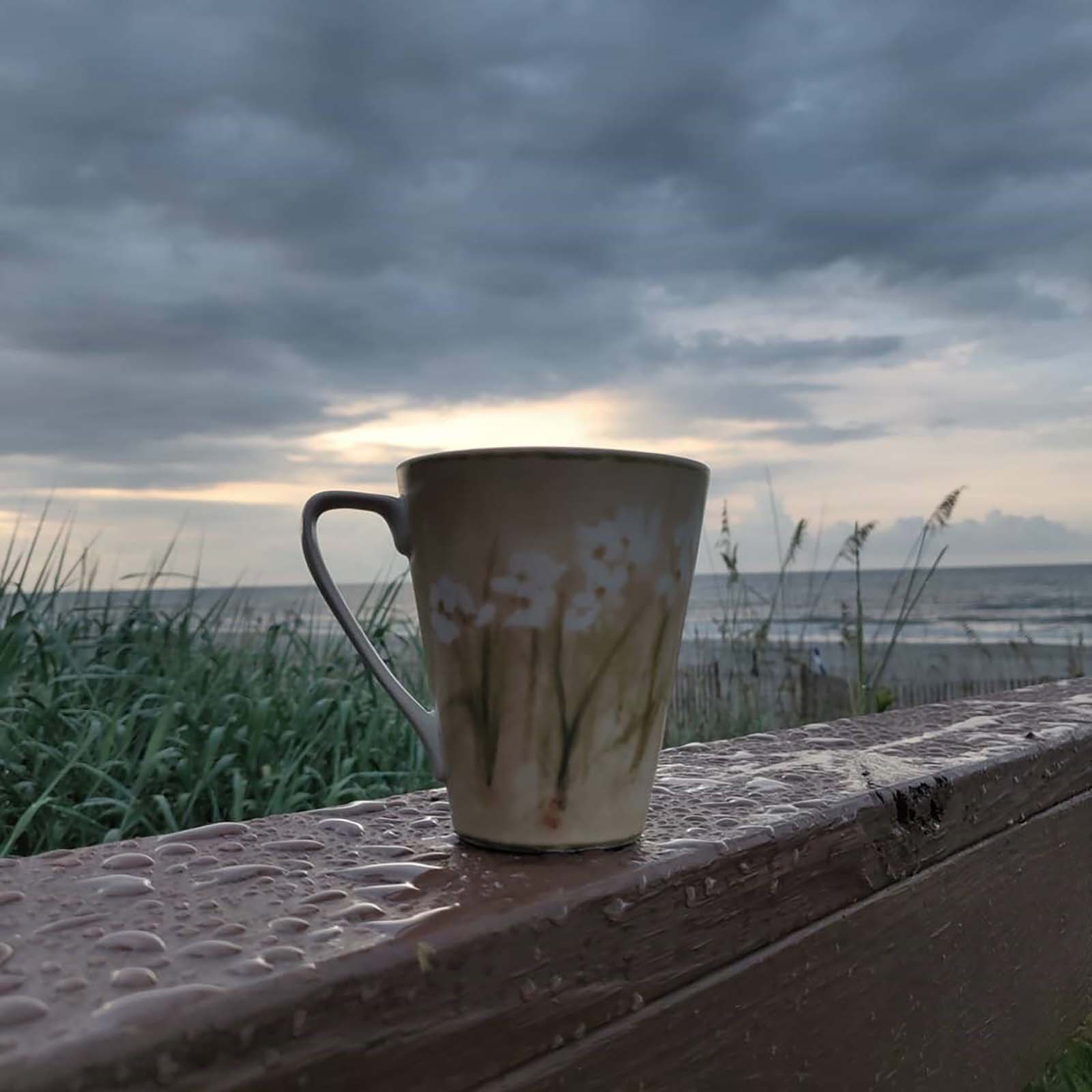 coffee cup with sunrise in background
