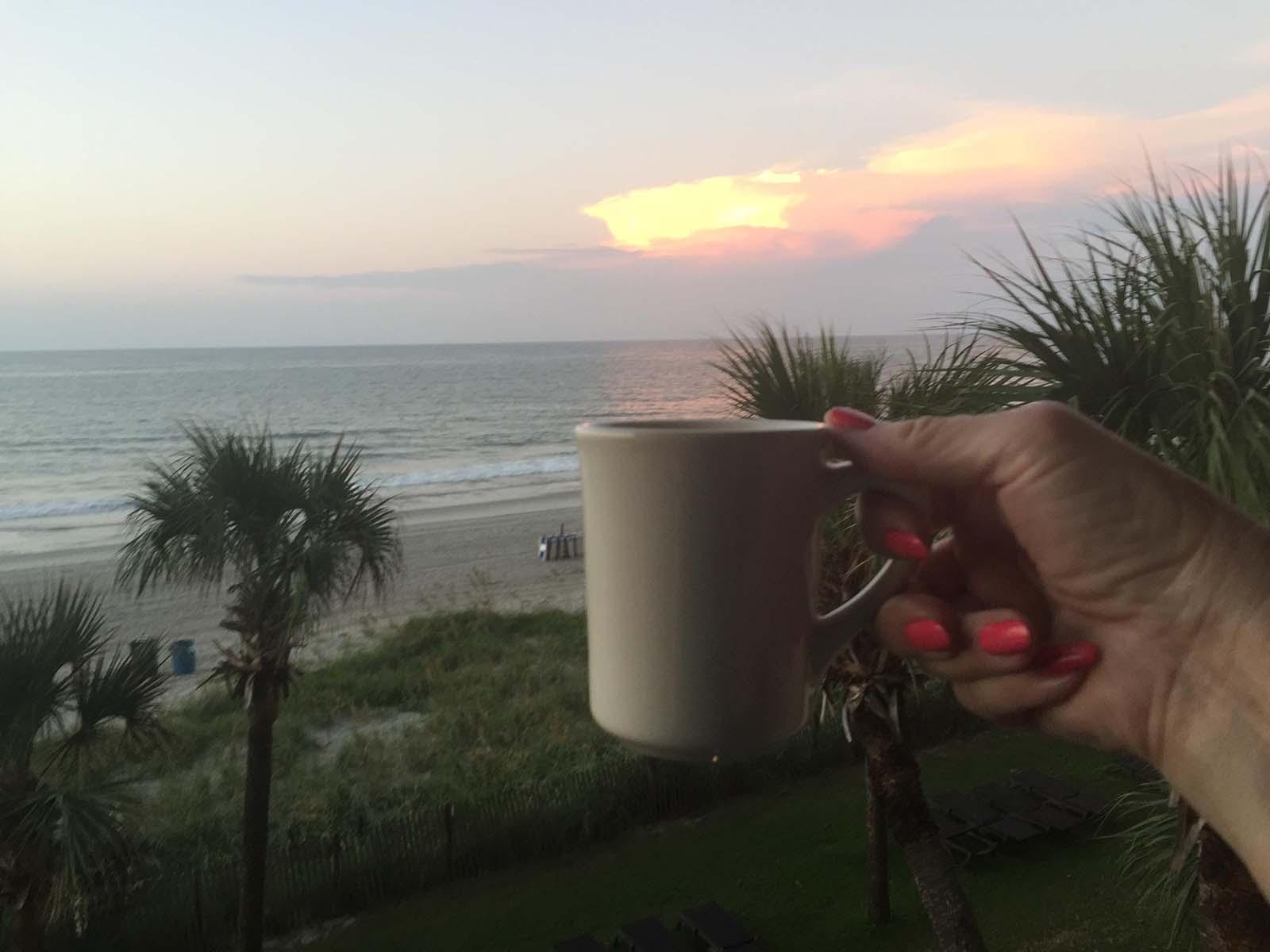 Holding coffee on balcony